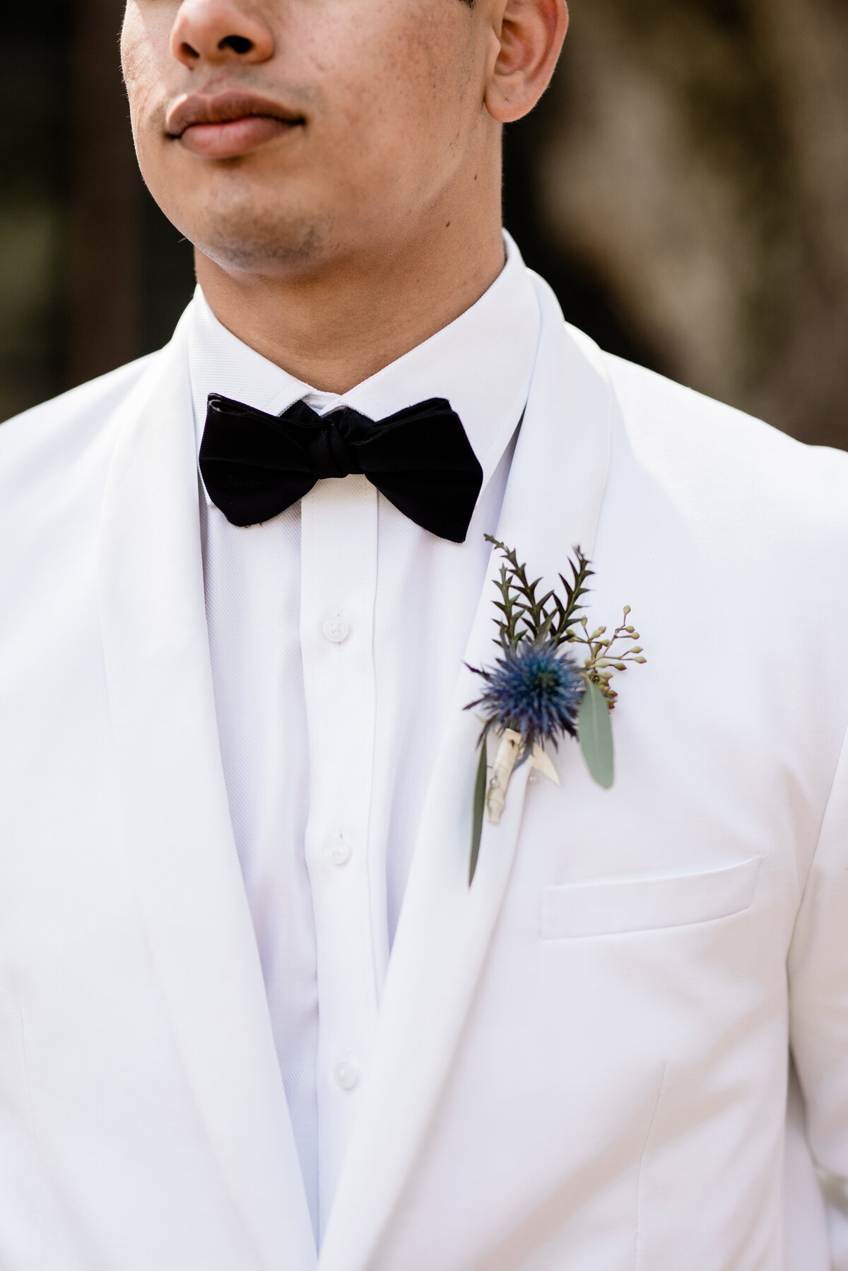 Groom white suit and boutonniere
