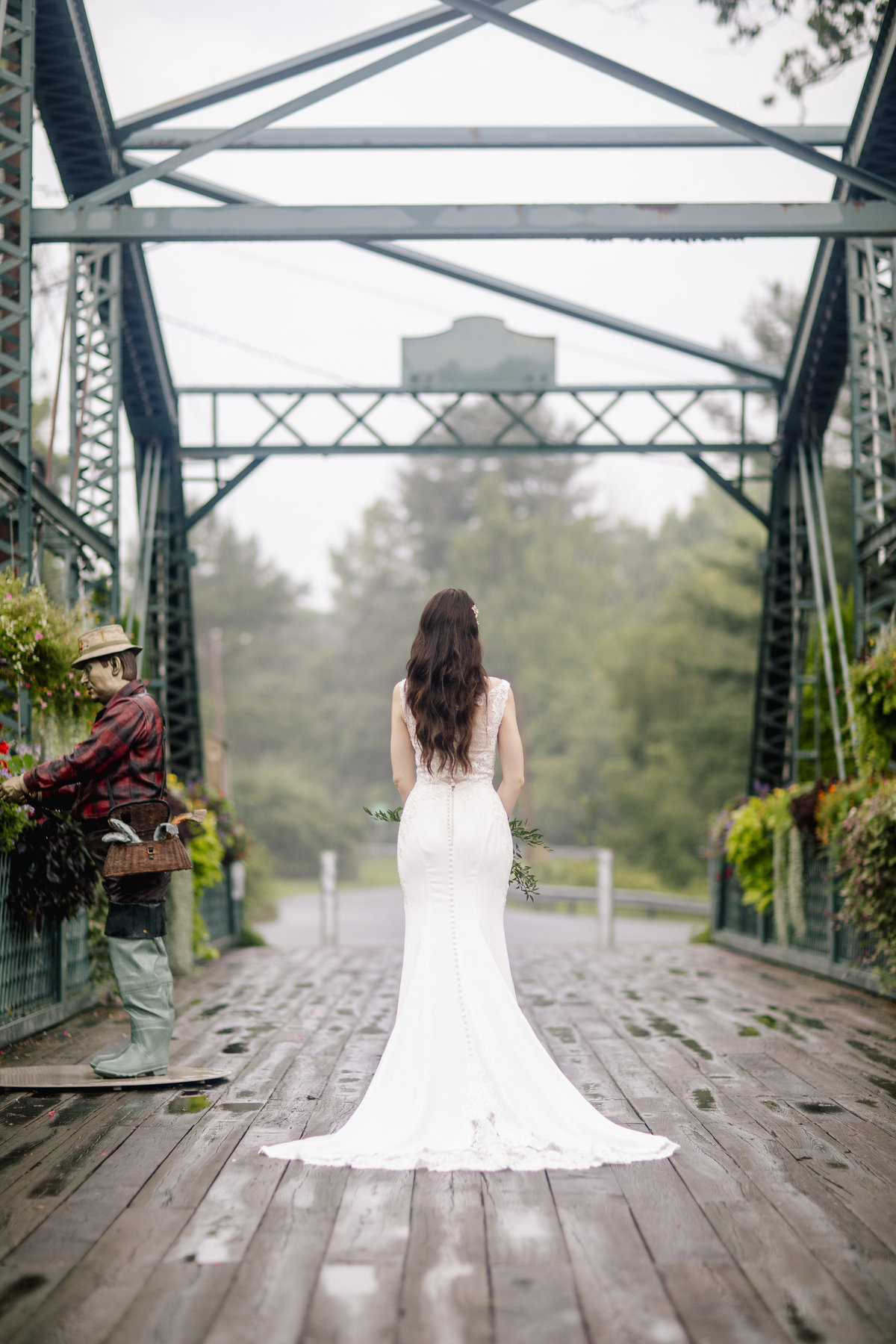 bride on bridge with flowers at riverview  wedding