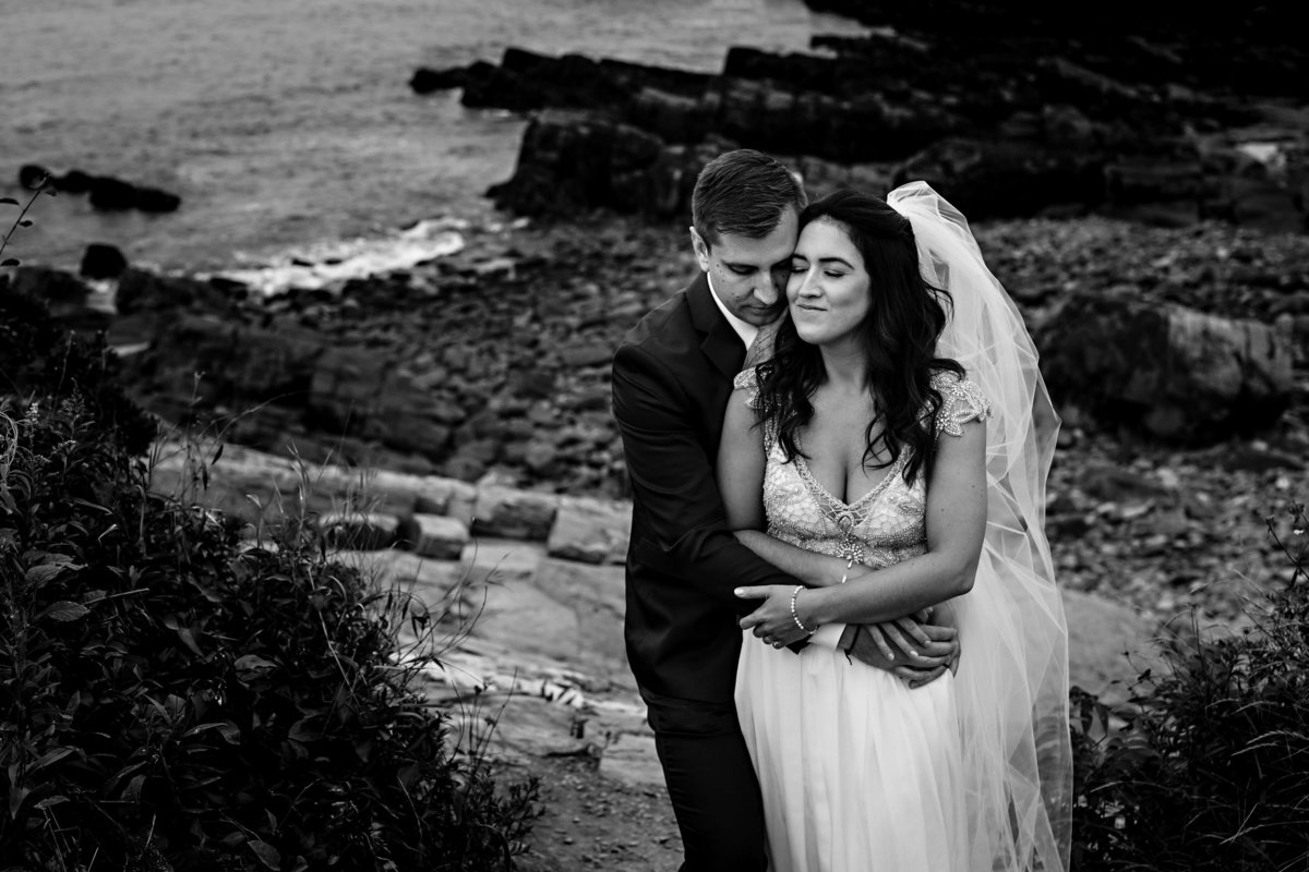 Cape Elizabeth Maine Elopement the newlyweds embrace on the rocks at Portland Headlight at Fort Williams