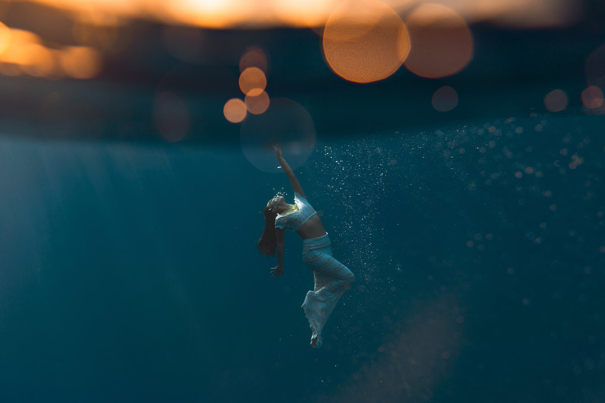 Bride wearing her wedding gown swims underwater in Maui at sunset as bokeh dances on the ocean's surface