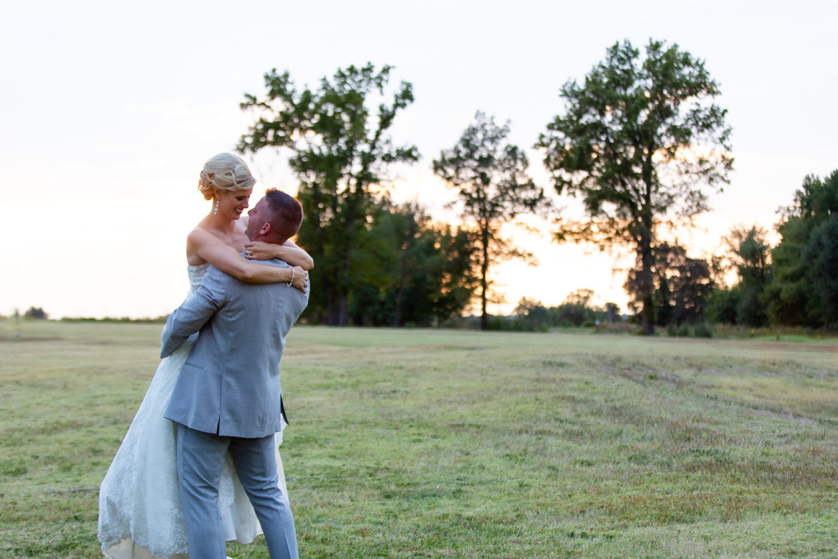 Romantic Sunset Fall Elopement  groom lifting bride in field at Kokopelli Golf Club  in Southern Illinois  by Amy Britton Photography Photographer in St. Louis