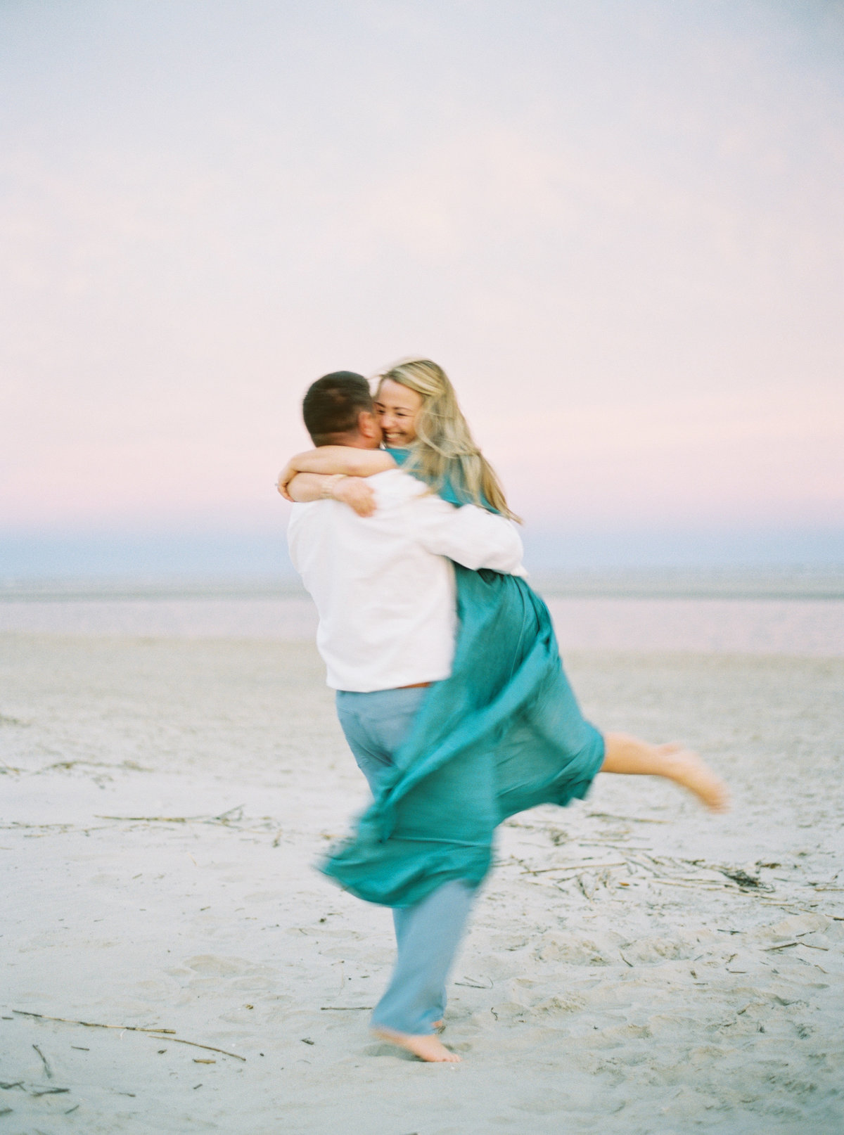Engagement photo with lots of emotion as couple spins on the beach.
