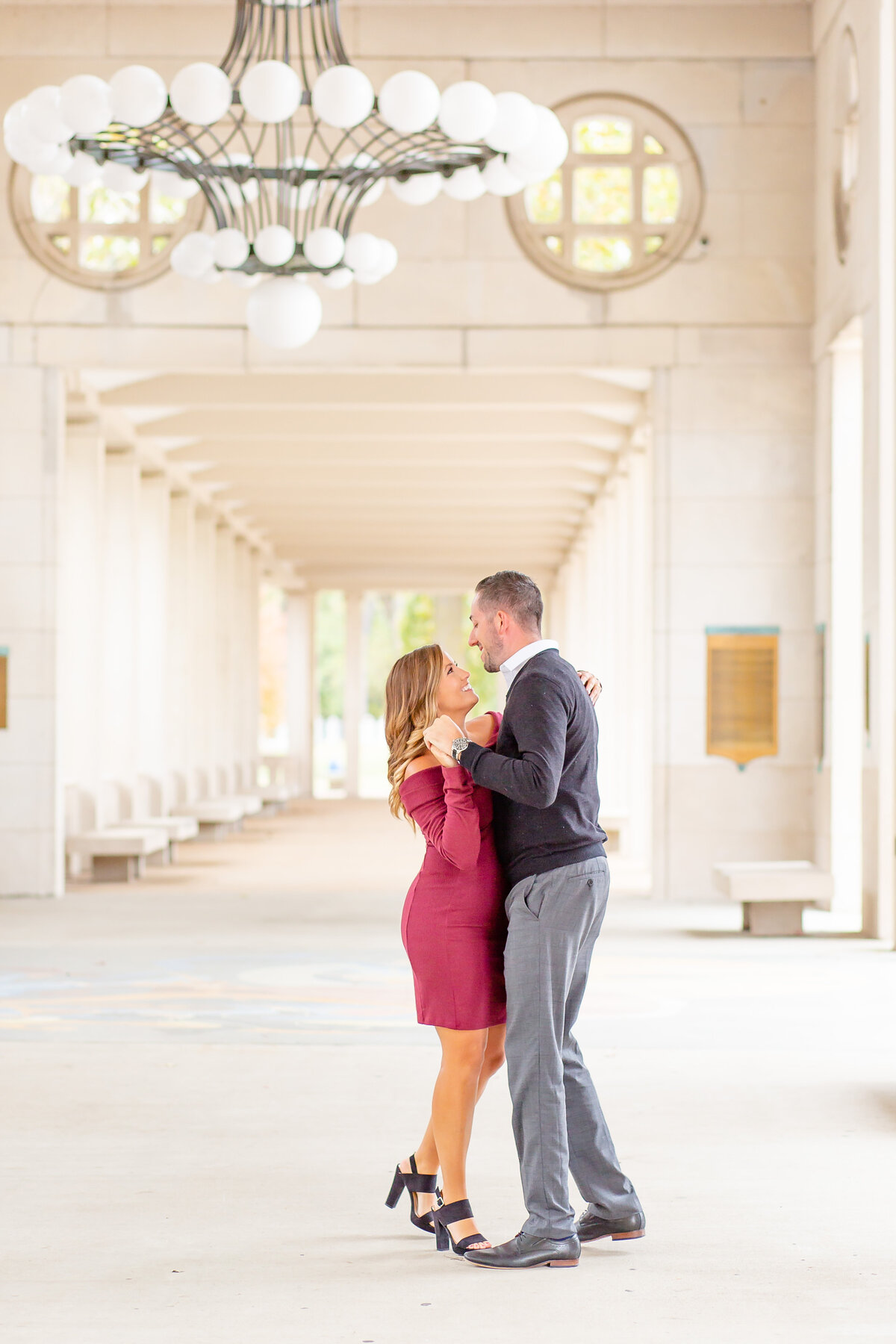 Fall Sunset Engagement  Session with pink off the shoulder dress couple dancing  under the chandelier at The Muny  in Forest Park in St. Louis by Amy Britton Photography Photographer in St. Louis