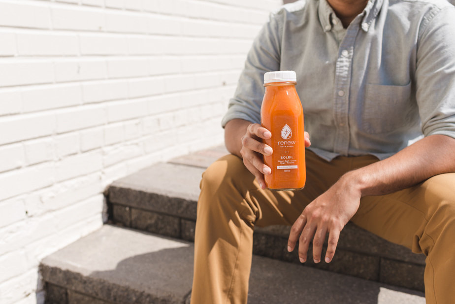 guy sitting on steps holding bottle of cold press juice
