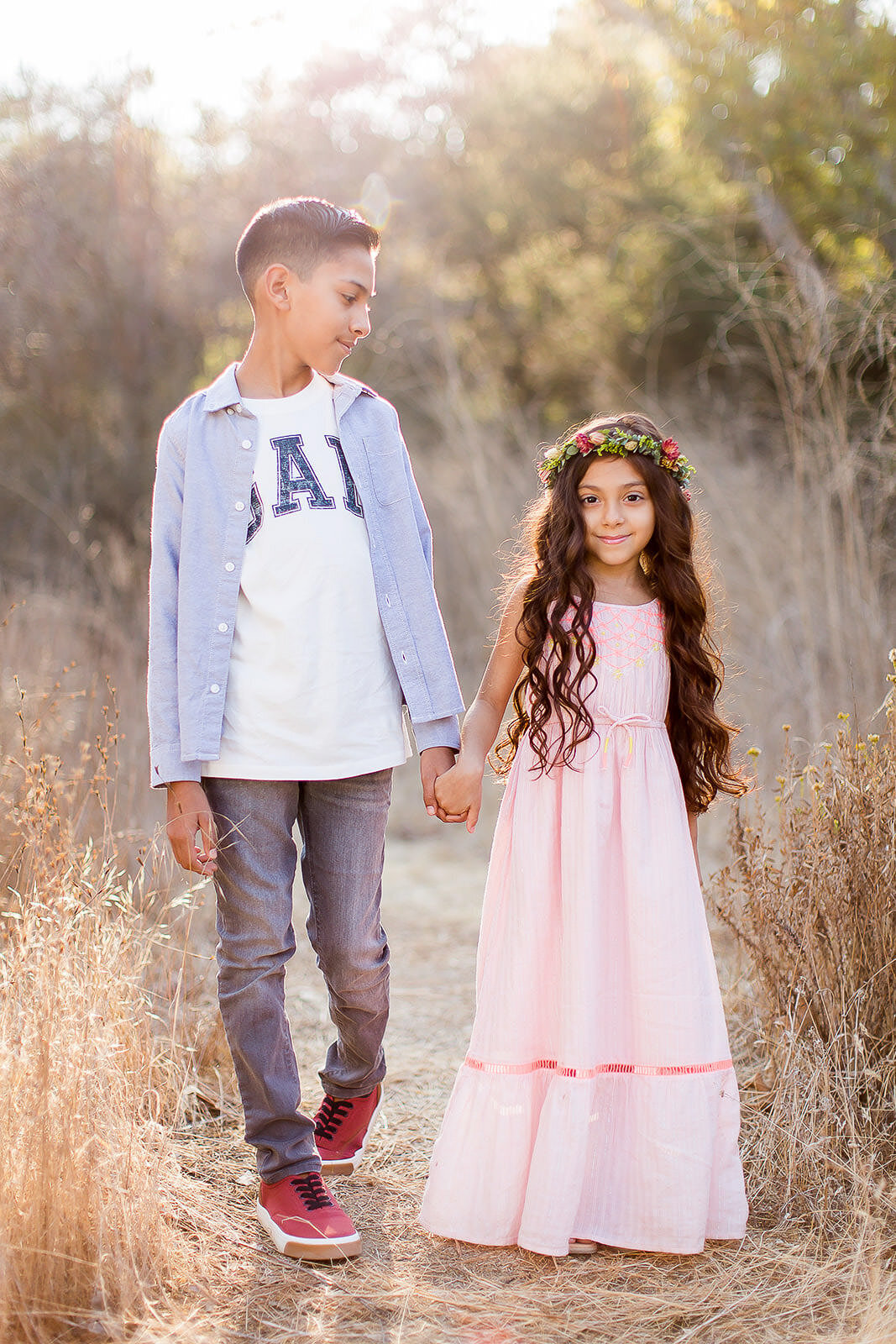 brother and sister holding hands walking through field