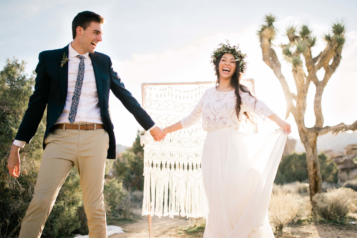 the couple laughs in front of their ceremony backdrop and joshua trees. the bride holds the corner of her skirt in the air