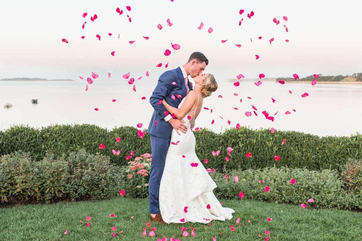 Couple kissing with flower petals at Wequassett