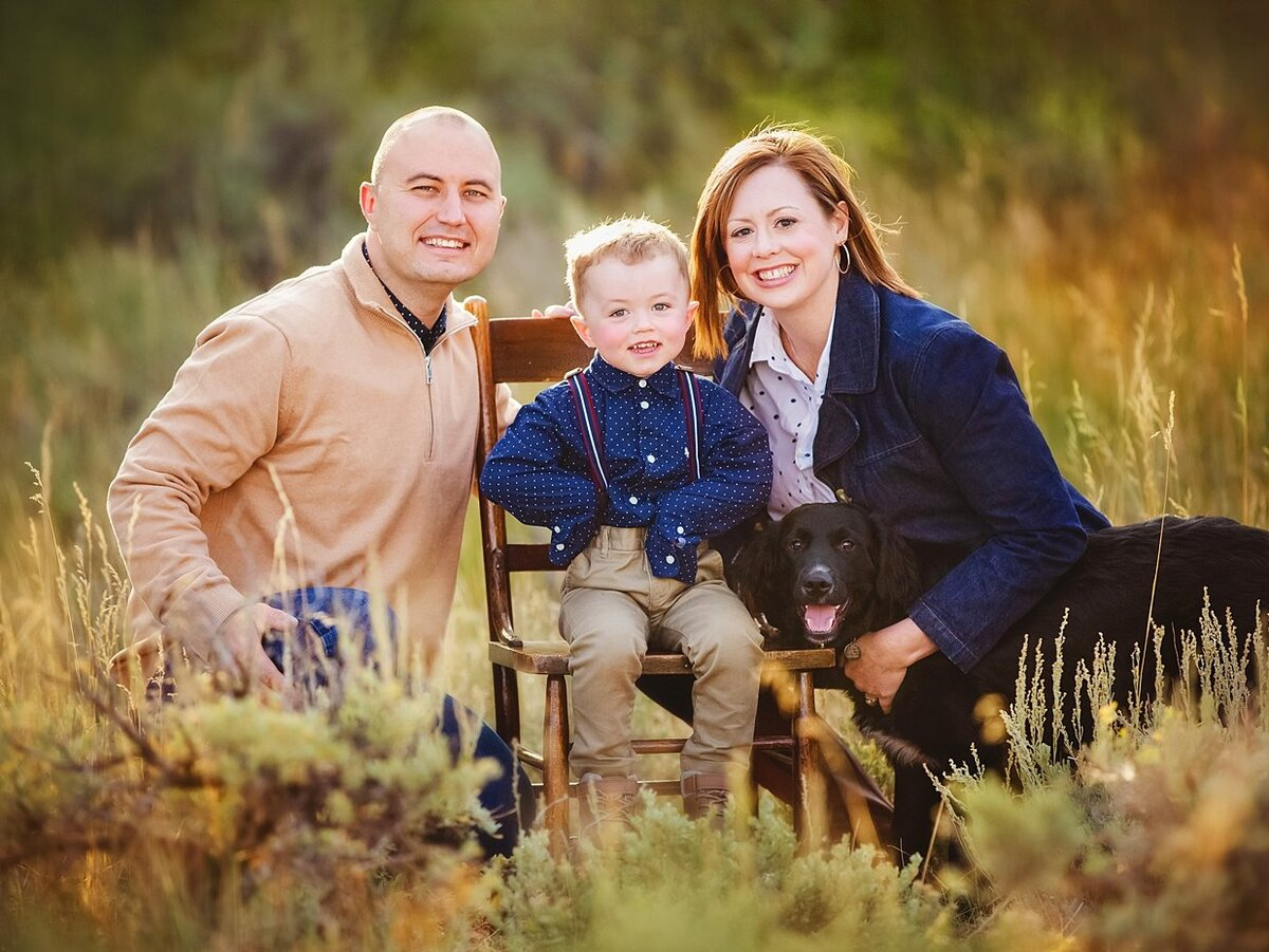 Fall colors in Laramie surround a family wearing tan and blue with an adorable little boy in suspenders.