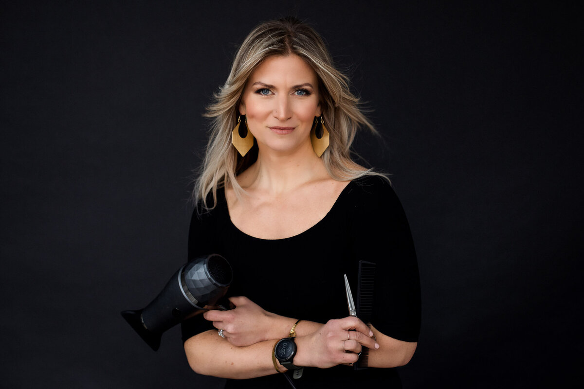 Business headshot of hairdresser holding hairdryer and scissors