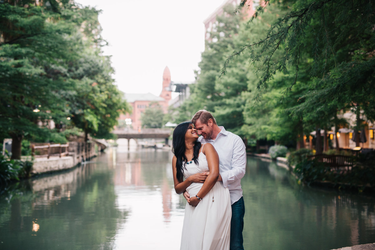 Pregnant couple holding each other in front of the San Antonio River Walk for their maternity photography session.