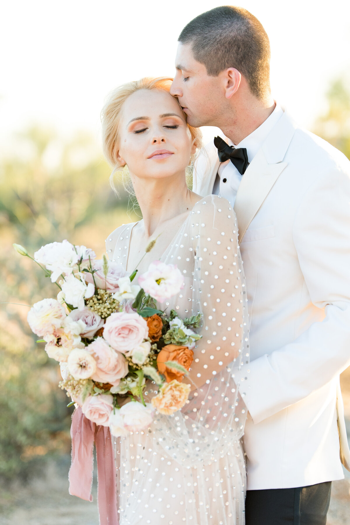 A groom kisses his bride lovingly on their wedding day at DC Ranch in Arizona