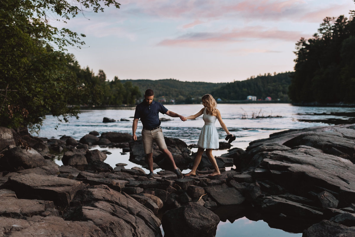 man holding his bride's hand as they walk across the rocks by the water