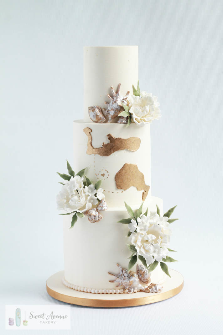 buttercream white  wedding cake with flowers and world map