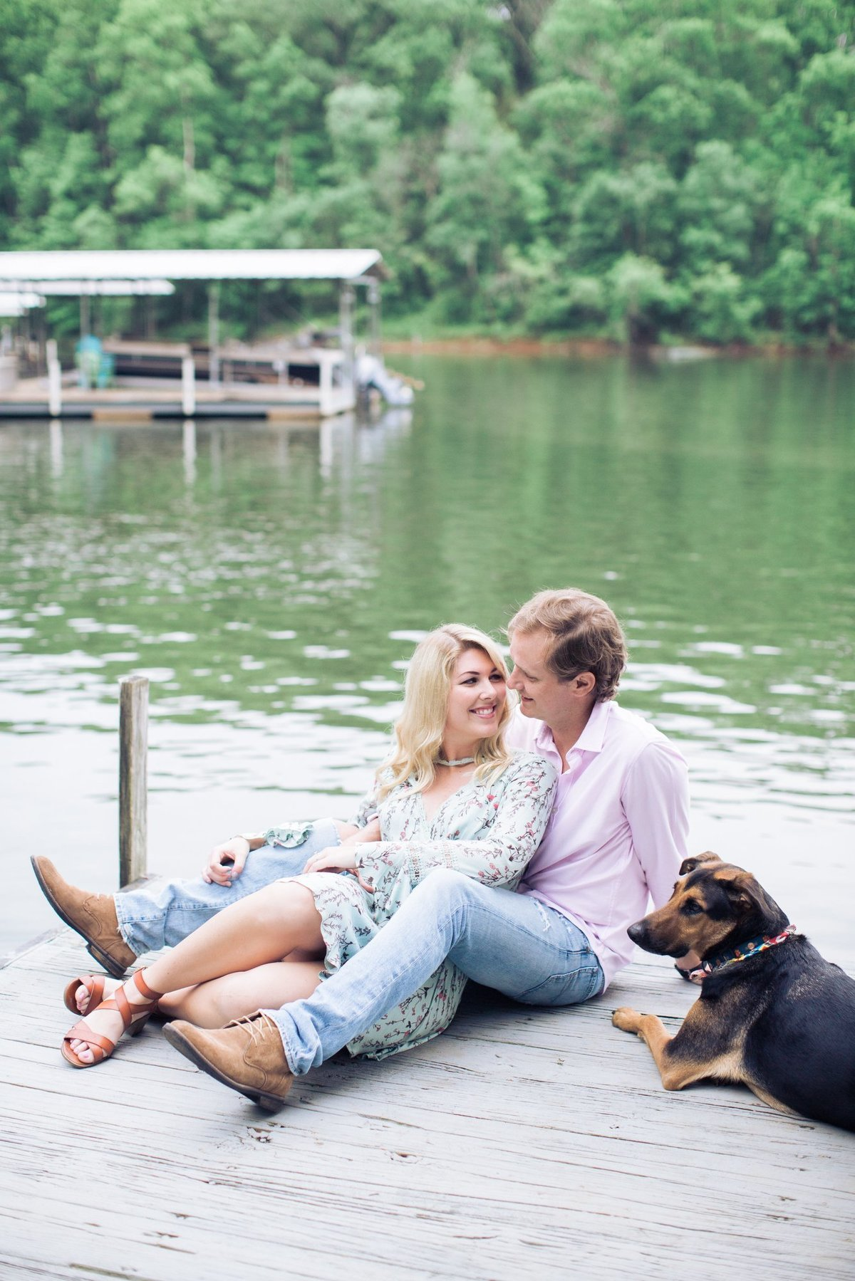 Wedding Photographer, couple sitting on a dock together with their dog
