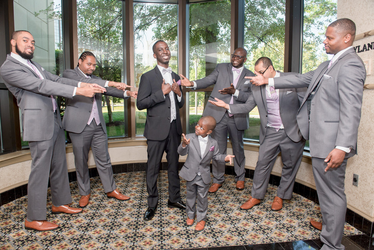 Smiling Groom and  pointing Groomsmen with cute little ringbearer