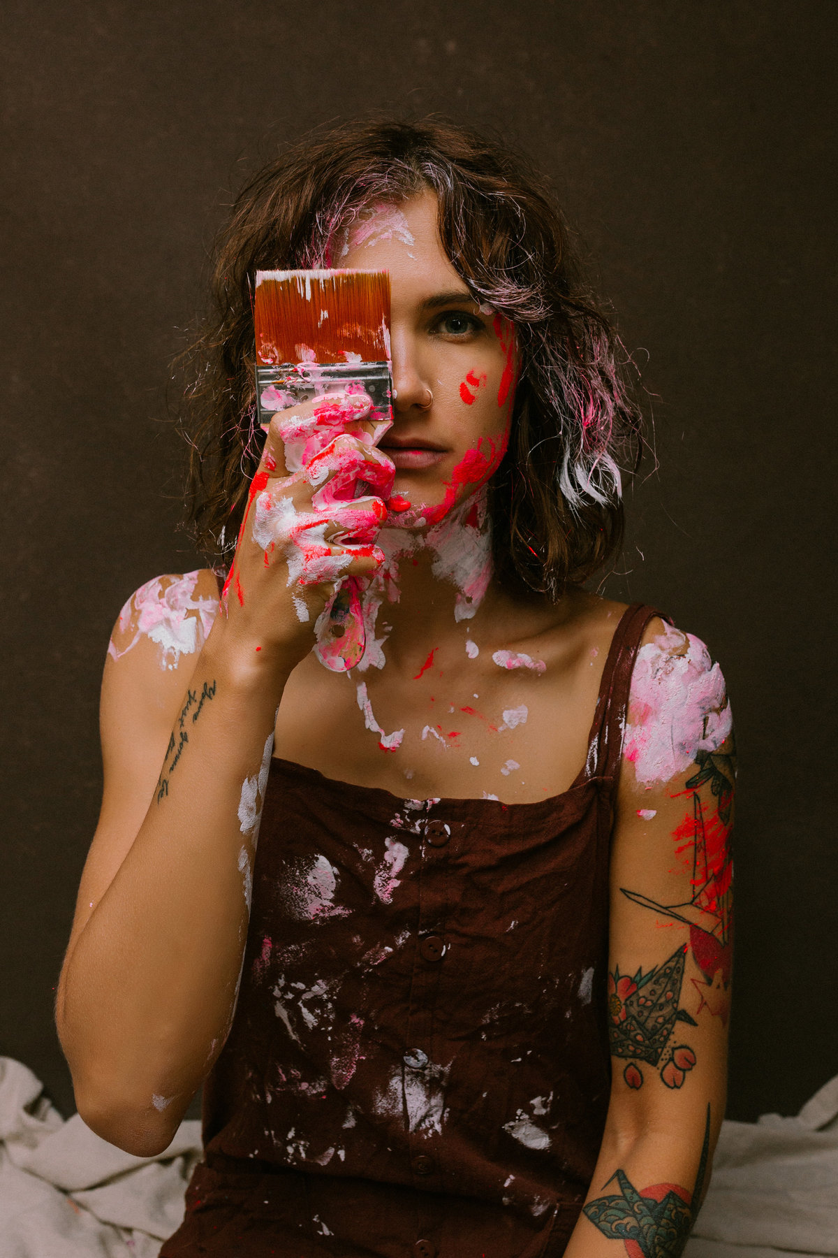 Portrait of a woman holding a paint brush in front of her face, with paint on her hands and shoulders.