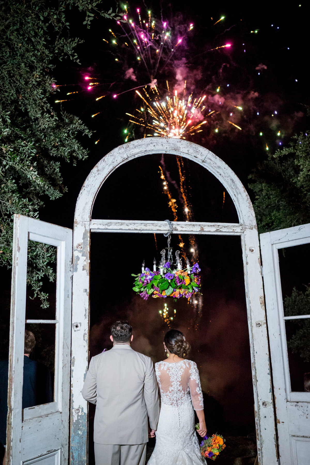 Bride and groom watch fireworks from outdoor altar wedding ceremony site for grand exit at Marquardt Ranch venue hill country