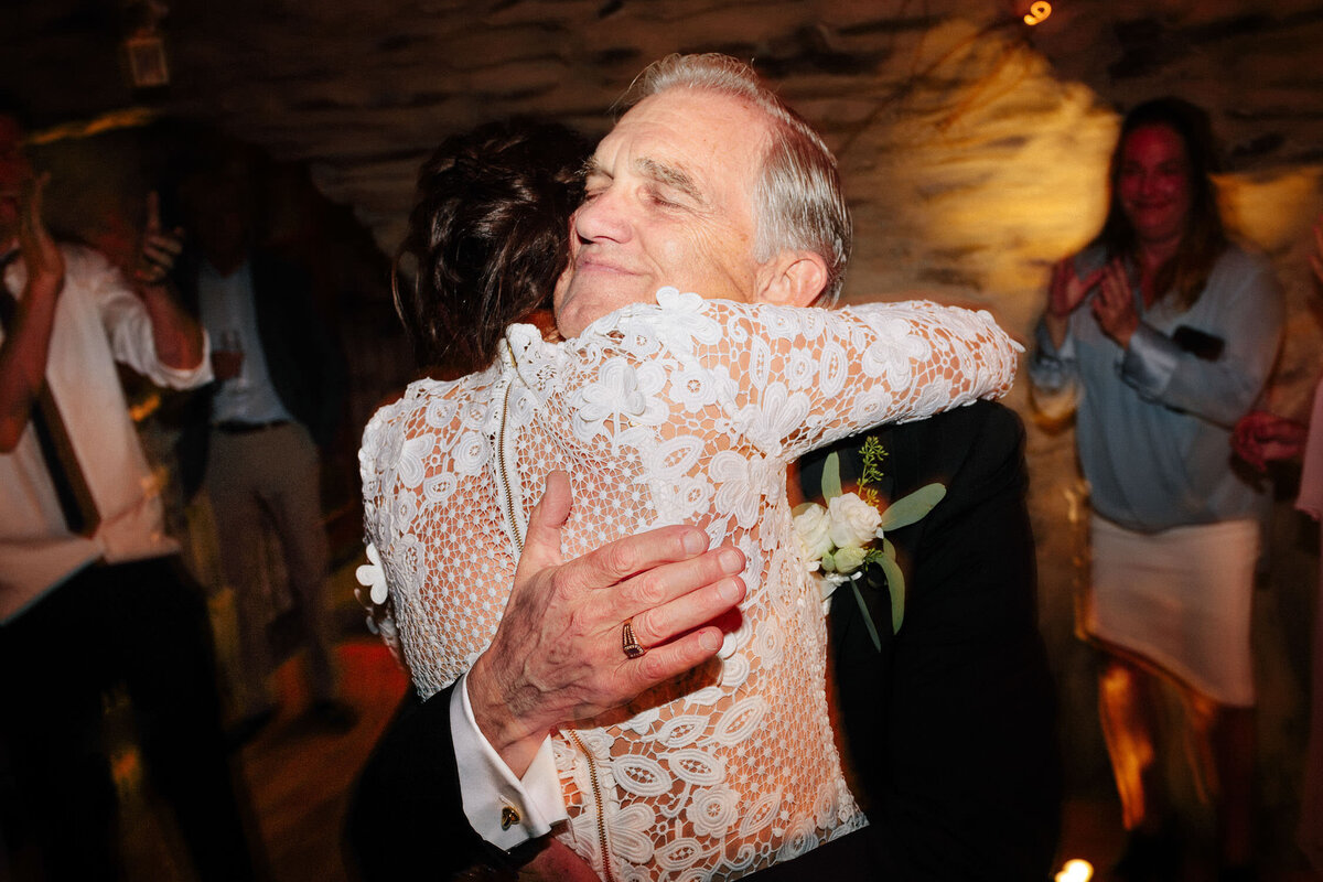 father of bride hugging daughter in white dress at wedding reception dance