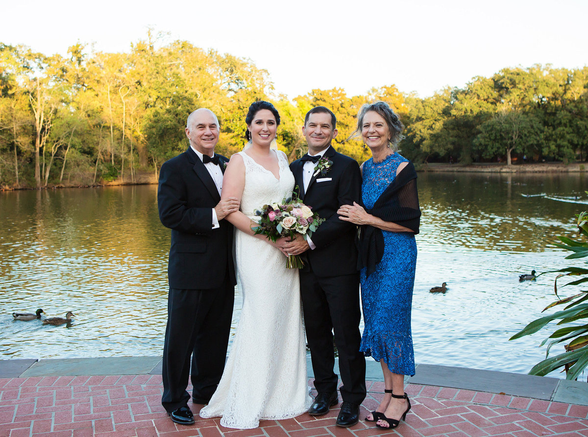 mother and father of the groom with a New Orleans bride and groom in front of a pond