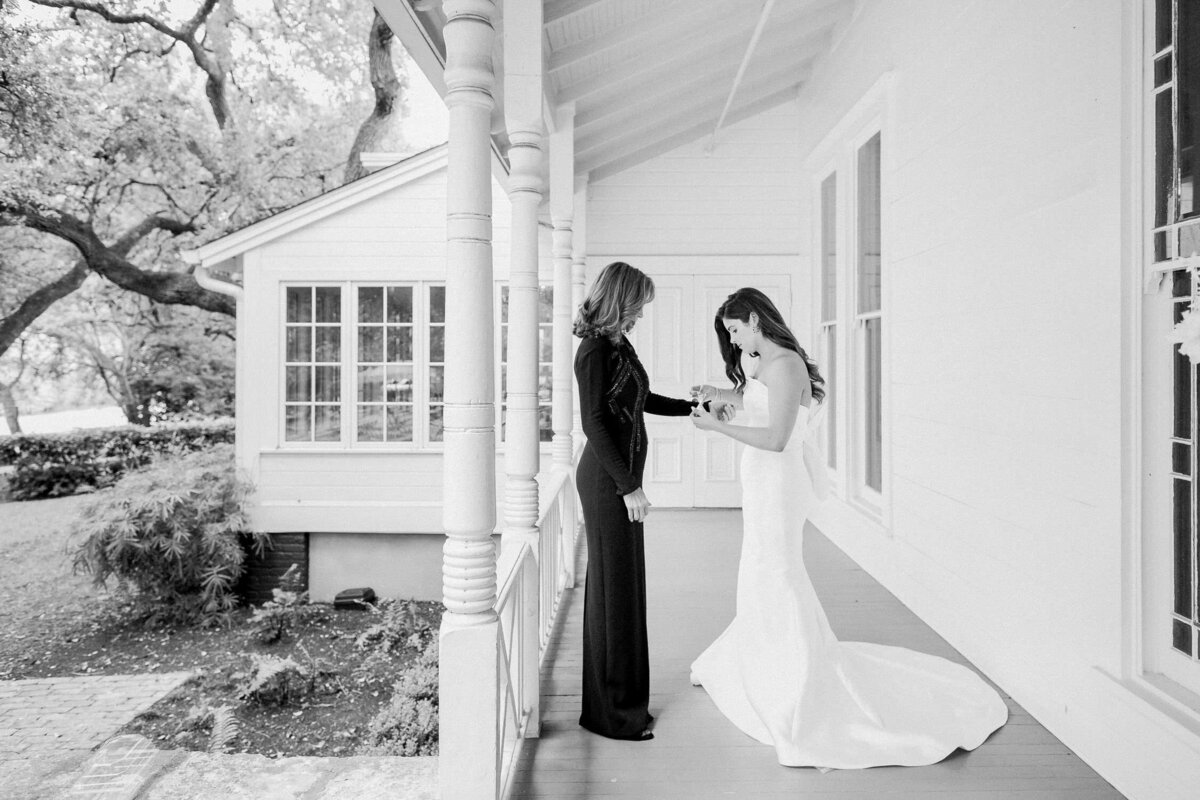 Bride on porch putting corsage on mother wedding day