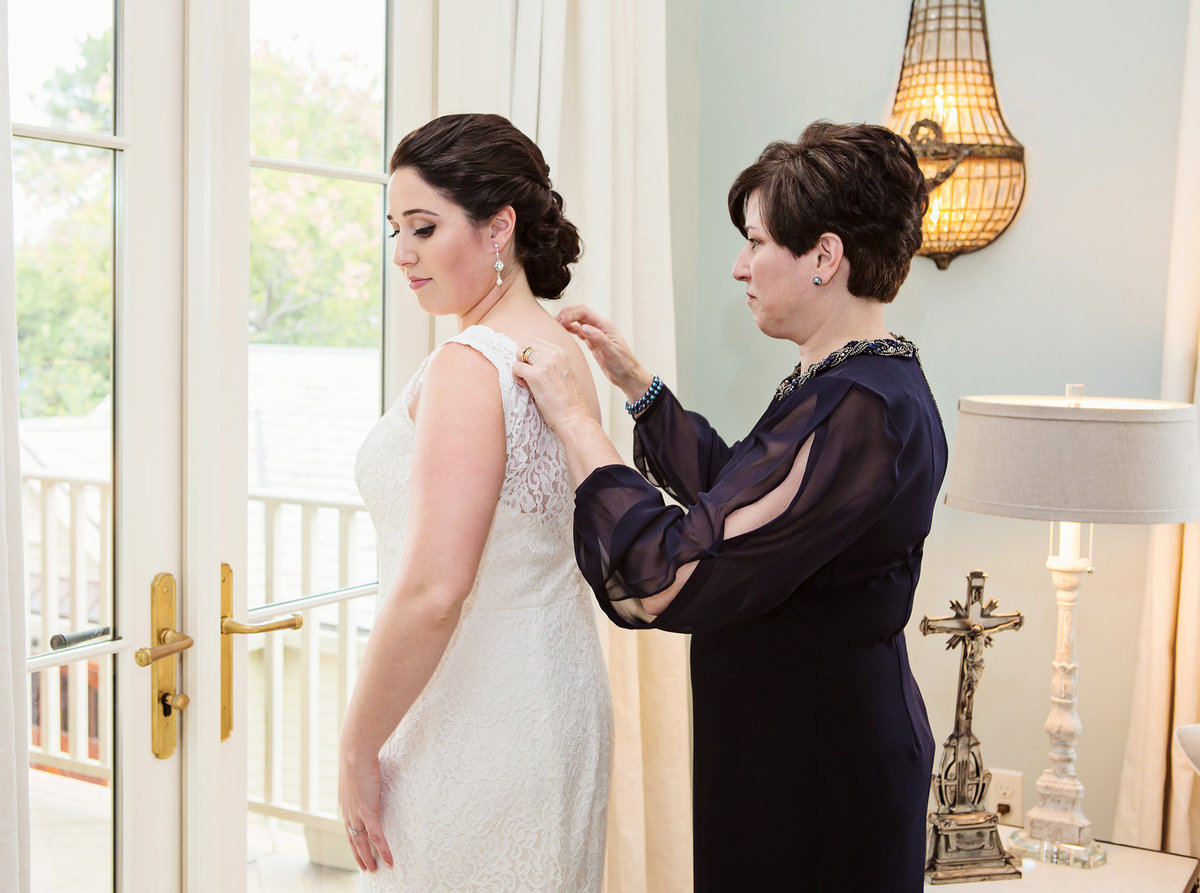 mom fixing new orleans bride's necklace before wedding