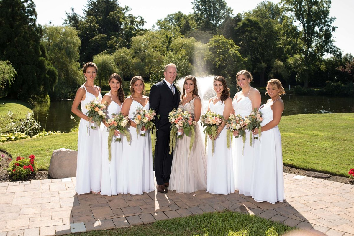 Bride and groom with bridesmaids outside at Flowerfield