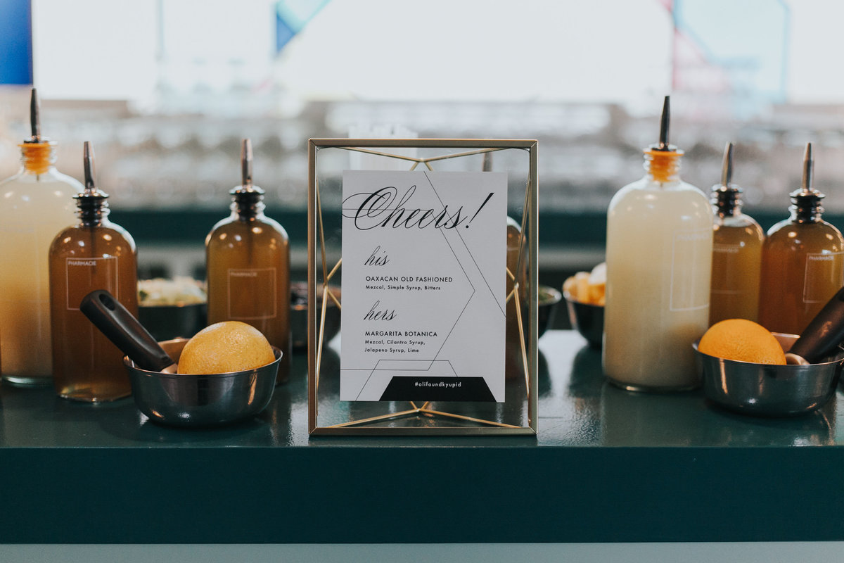 Wedding cocktail hour bar sign with gold geometric frame at The Fig House