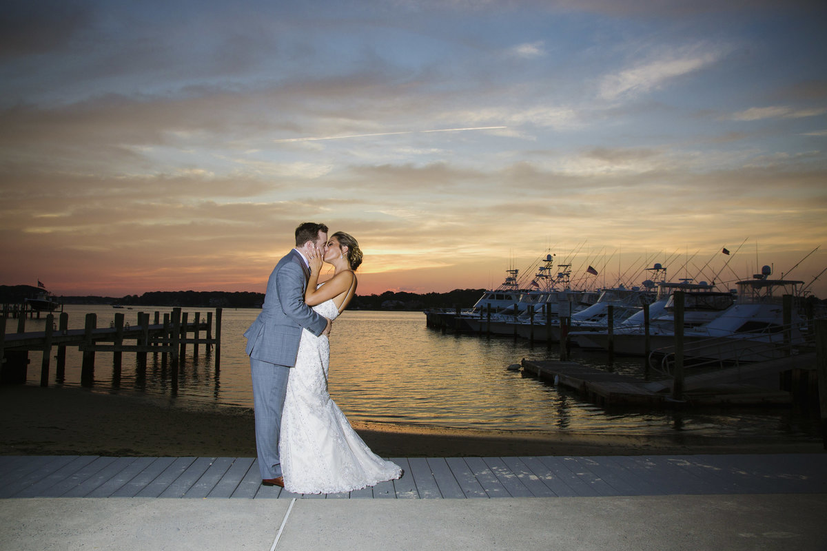 bride and groom kissing at sunset at clarks landing yacht club wedding