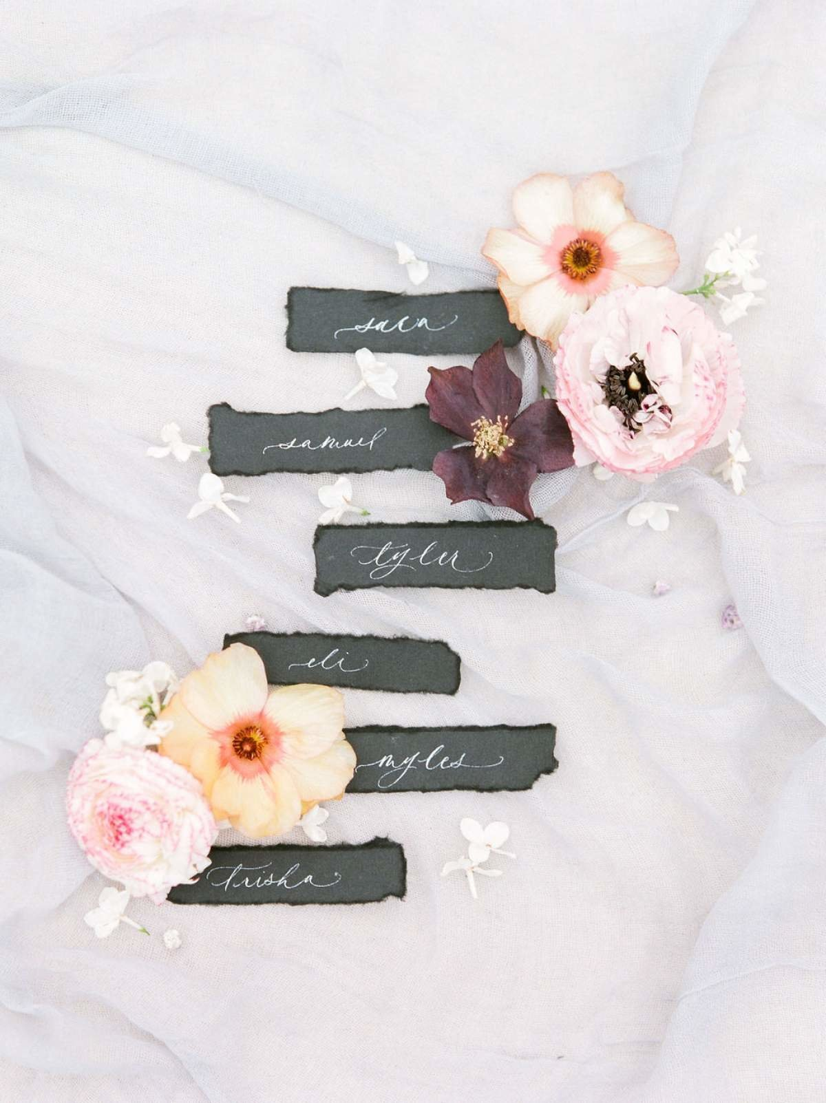 Black-Calligraphy-Escort-Cards-Flatlay-with-flowers