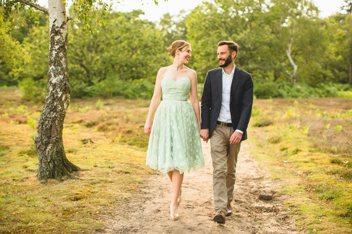 couple with green wedding dress holding hands walking