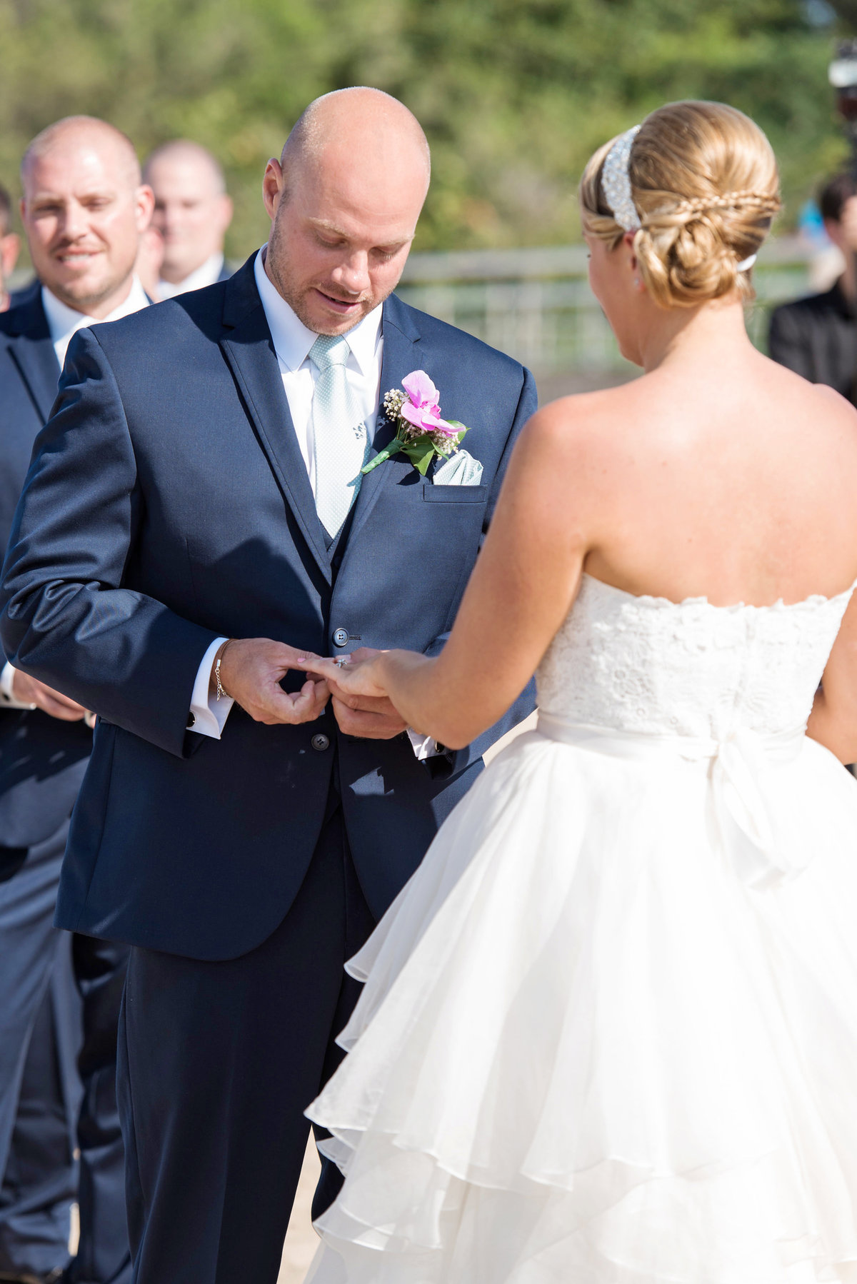 photo groom putting ring on bride during ceremony reception at Pavilion at Sunken Meadow