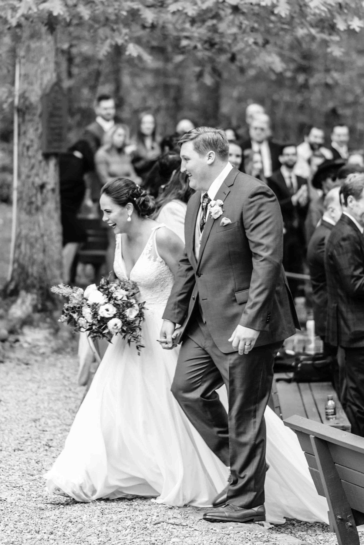 bride and groom walk down the aisle after ceremony with laughter on their face in northern virginia