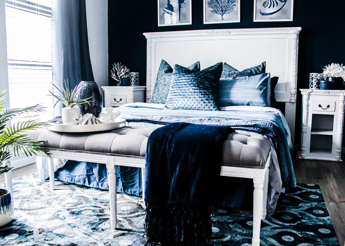 Navy painted walls frame a white luxury bed in a luxury blue bedroom.