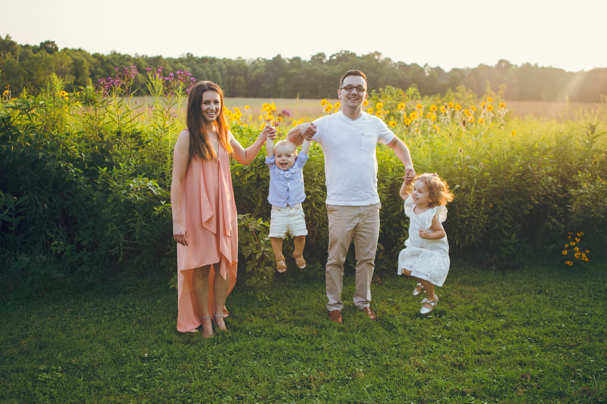 Family jumping in sunny field {Mississauga Family Photographer}