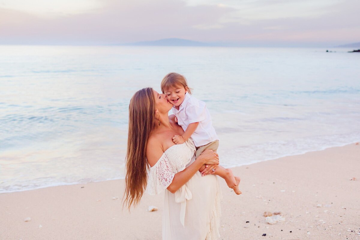 Mother holds son at White Rock beach and kisses him on the cheek while smiling