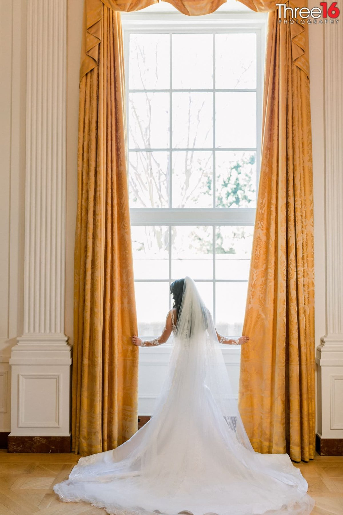 Bride poses in front of a large window with her gown train fanned out