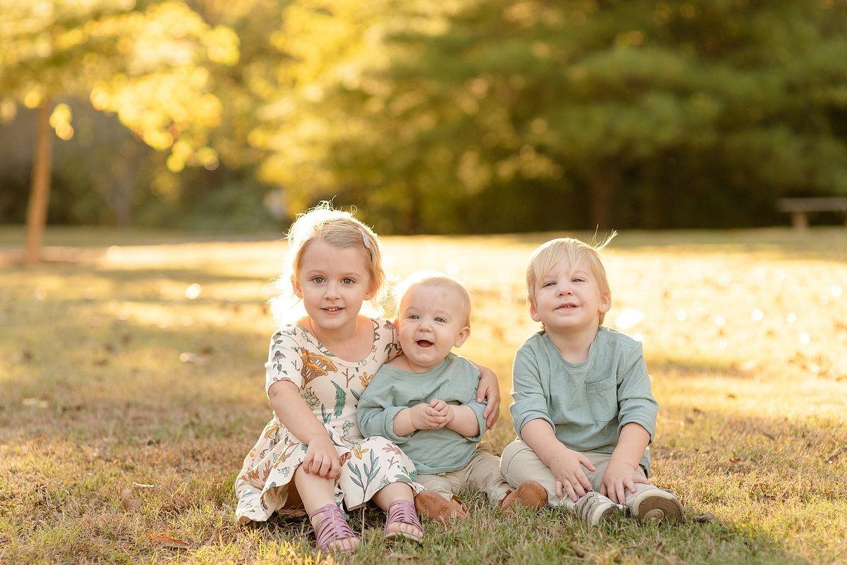 Three Siblings Sitting together during the golden hour for family portraits in Nashville, TN by Dolly DeLong Photography