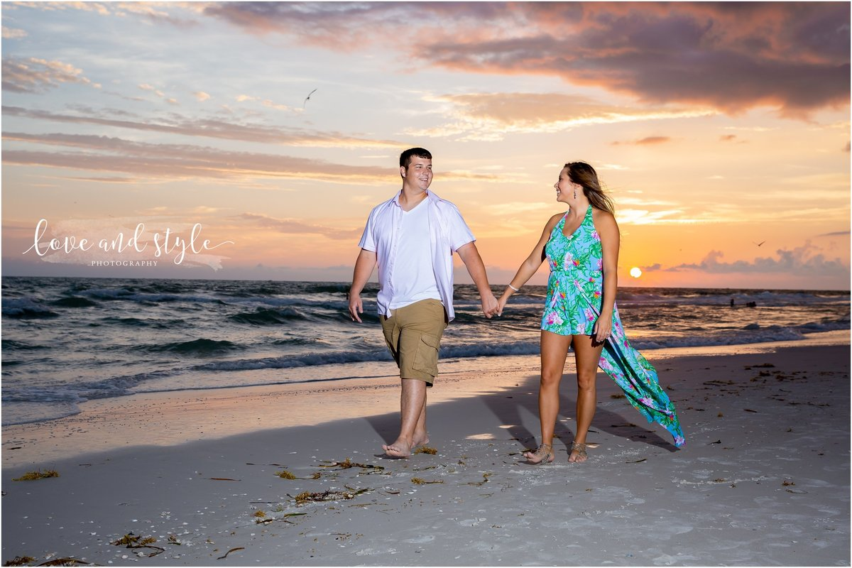 Engagement Photography on Bradenton Beach during sunset with couple holding hands and walking on the beach