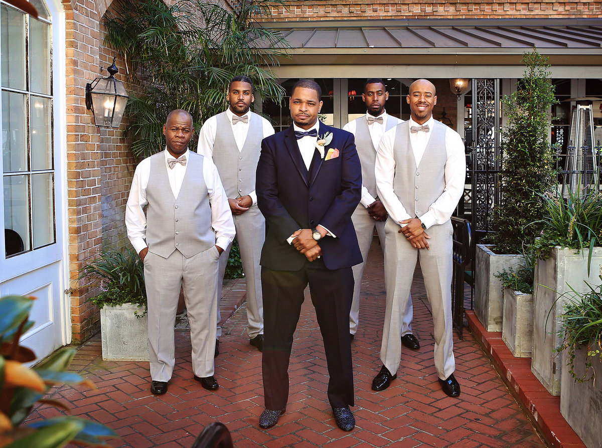 wedding portrait of groom and his groomsmen in the courtyard of the Chateau LeMoyne hotel