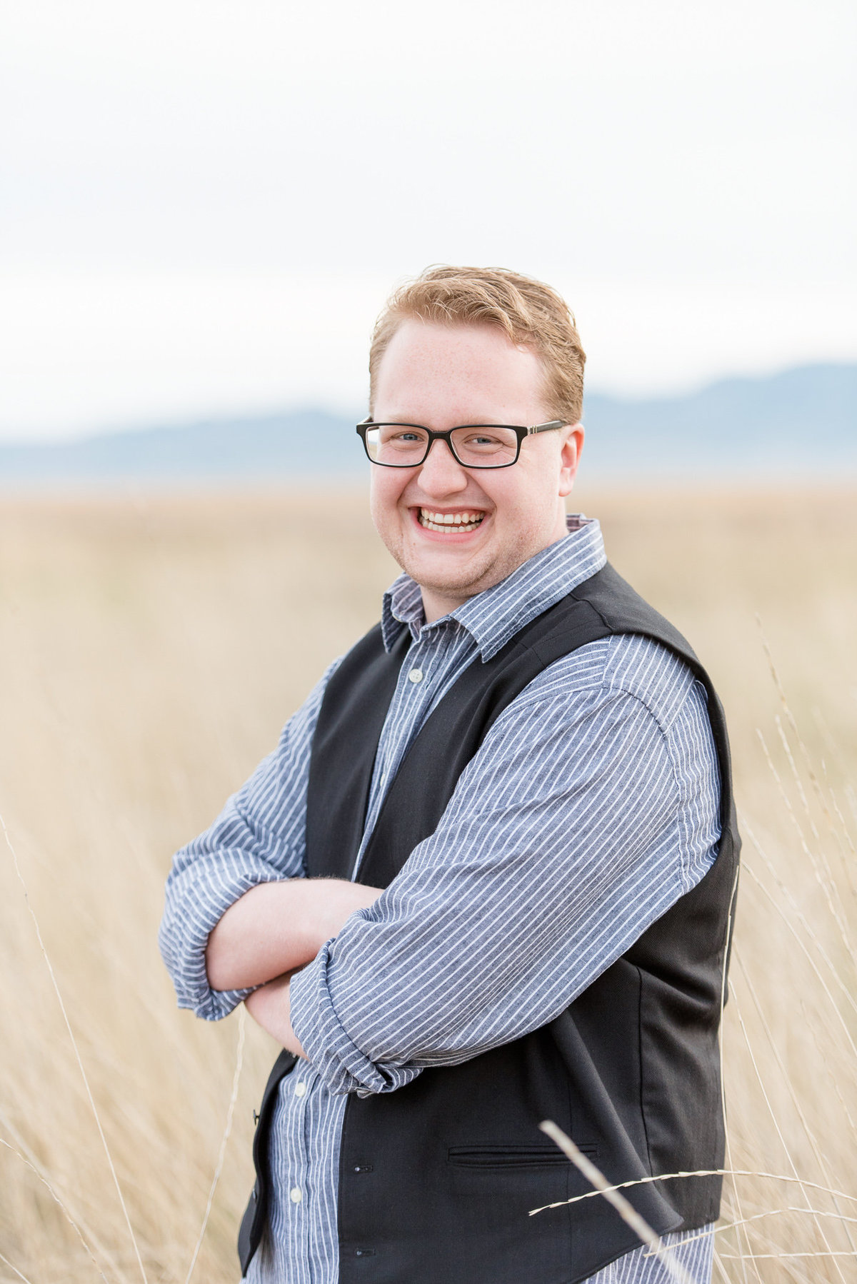 senior boy laughs at the camera while folding his arms in layton utah