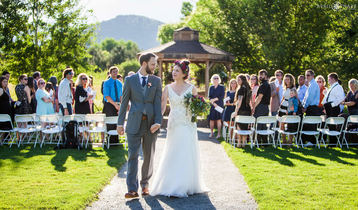 Bride and groom walk out together from their Chatfield Farms Wedding Ceremony in Colorado