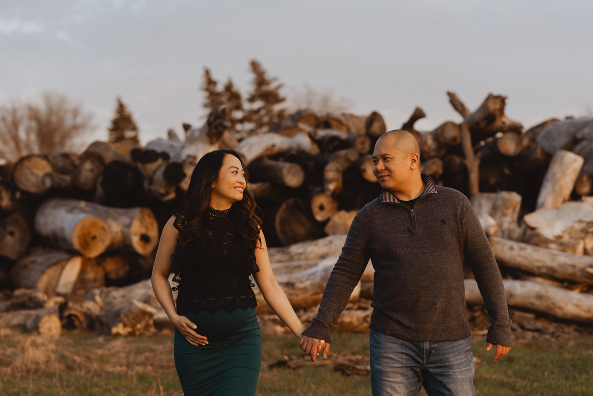 expecting parents walking through field with tree logs behind them