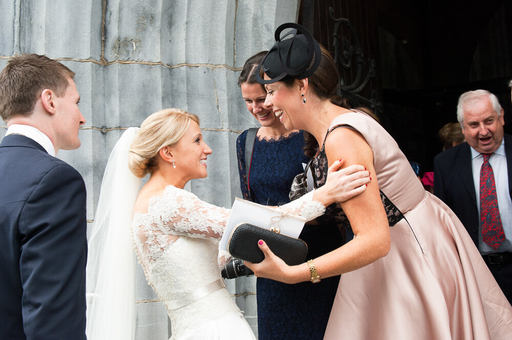 blonde bride wearing an a-line, lace, sleeved dress with satin waistband embracing her friends outside Killarney cathedral