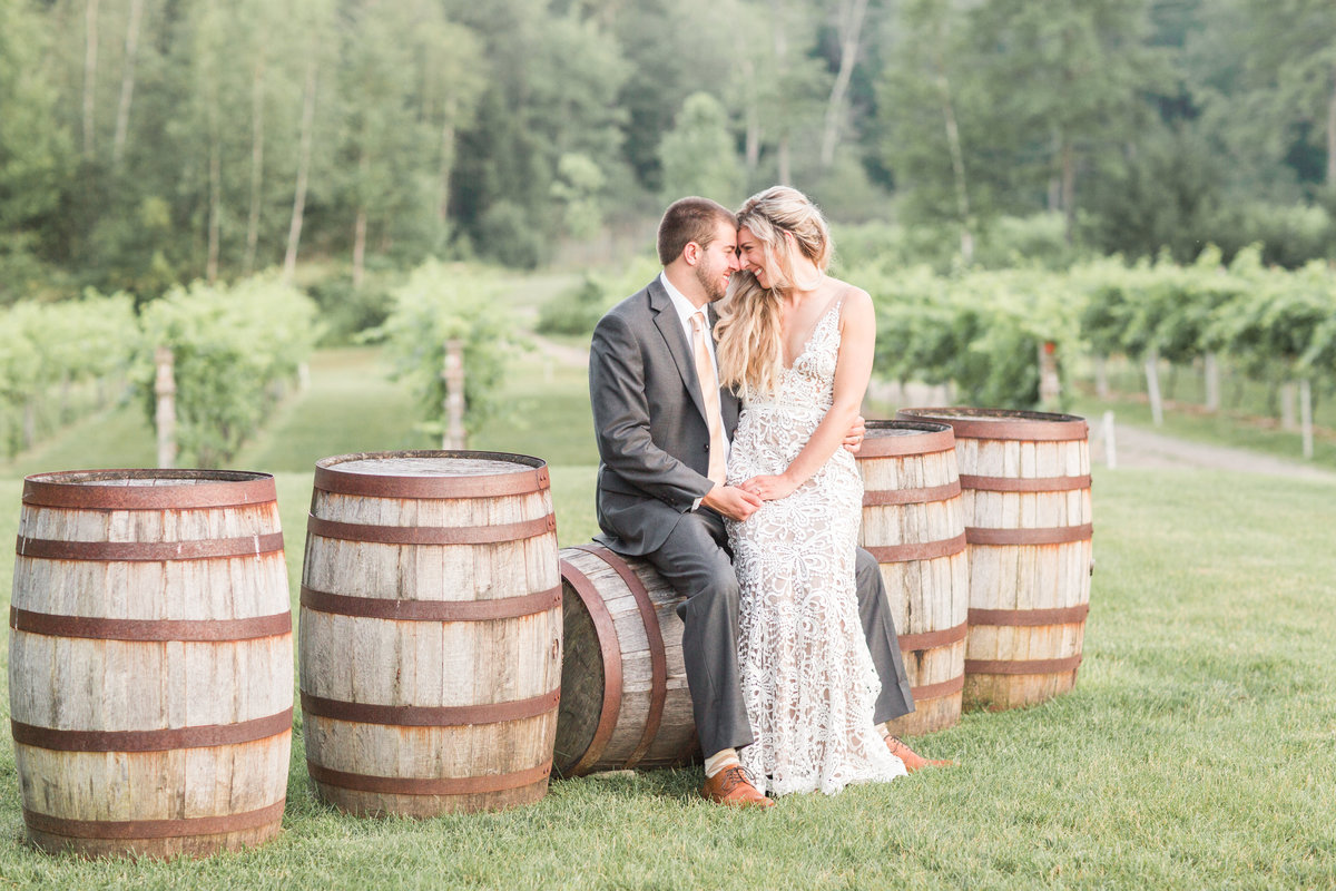Bride and groom sitting on wine barrels at Zorvino Vineyards