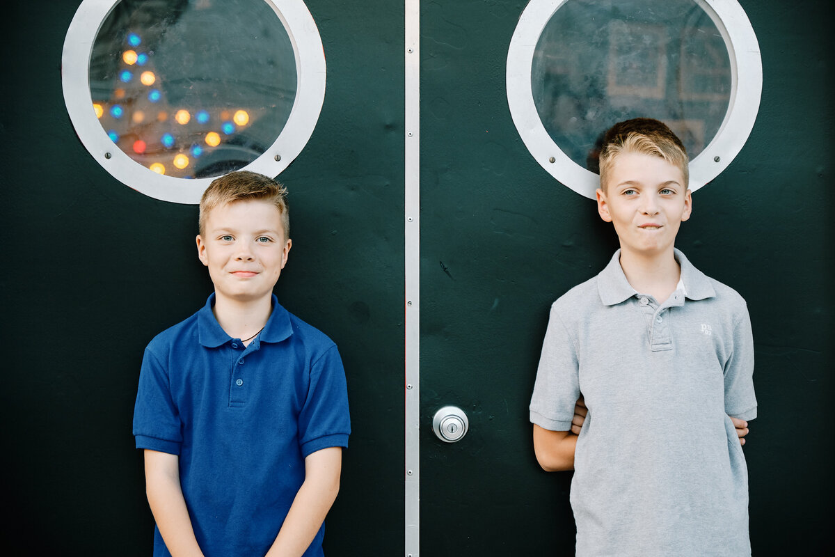 Two boys posing in front of unique door family portraits