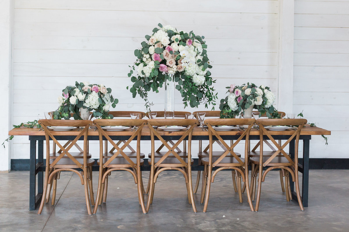 Tall garden centerpiece with wooden table and crossback chairs