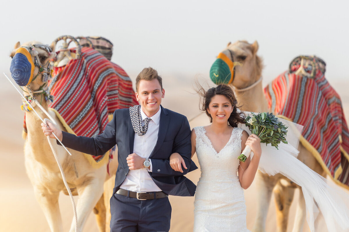 Portrait of the bride and groom with two camels celebrating their wedding in Dubai for a photoshoot organized by Lovely & Planned