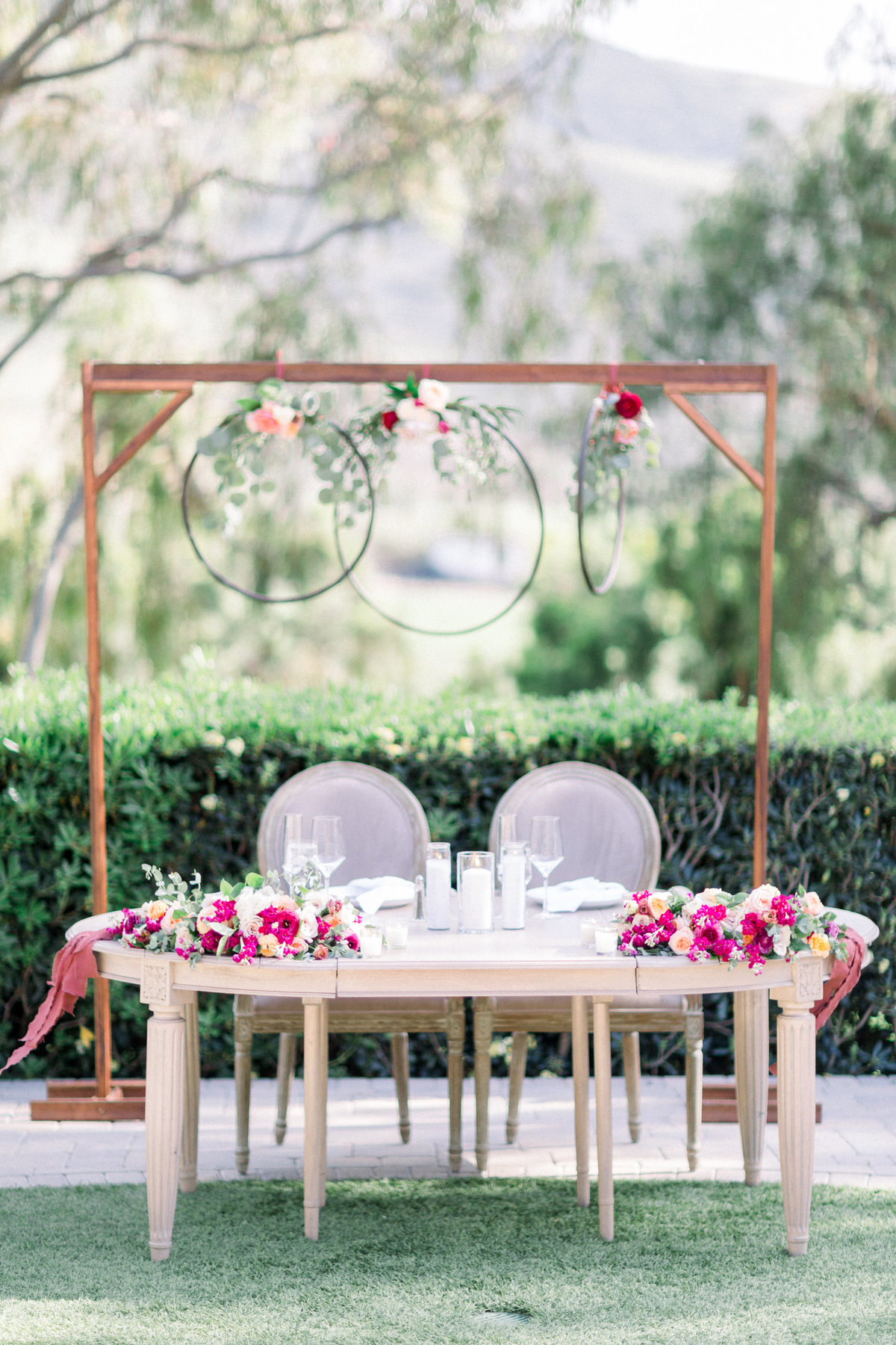 Wedding reception sweetheart table with hanging circle floral arrangements and mauve, pink and orange flowers at Maravilla Gardens