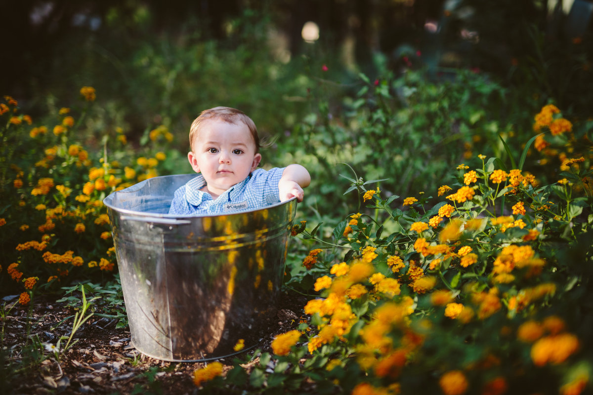 Toddler baby sitting in a silver bucket in a field of flowers posing for San Antonio Photographer Expose The Heart