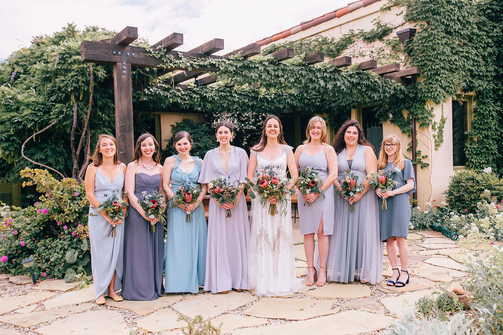 bride with bridesmaids in ombre blue mismatched bridesmaid dresses at wedding in Ojai